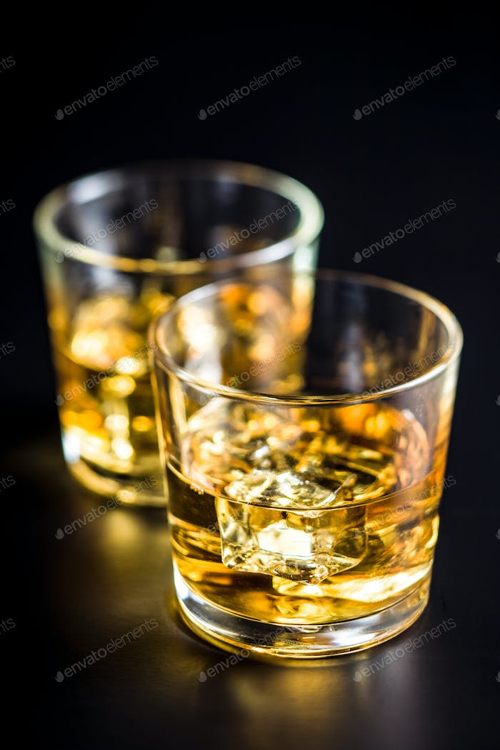 Glass of alcoholic drink with ice cubes on black table.