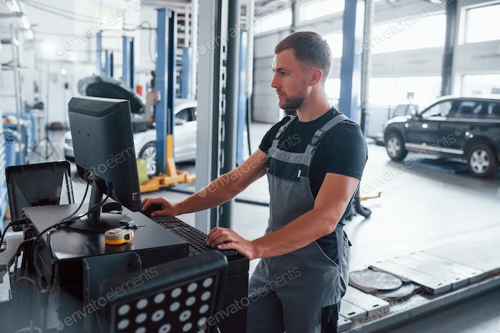 Searching information. Man at the workshop in uniform use computer for his job for fixing broken car