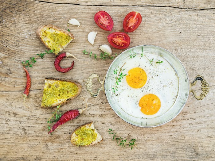 Breakfast set with roasted eggs, bread toasts with pesto souce,