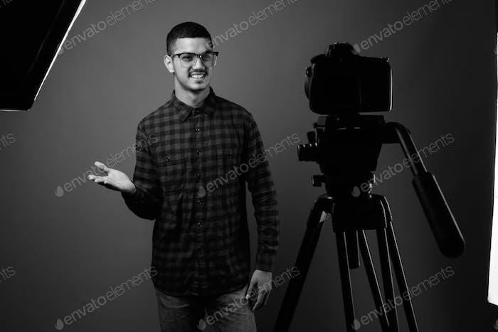 Young multi ethnic Asian man against gray background