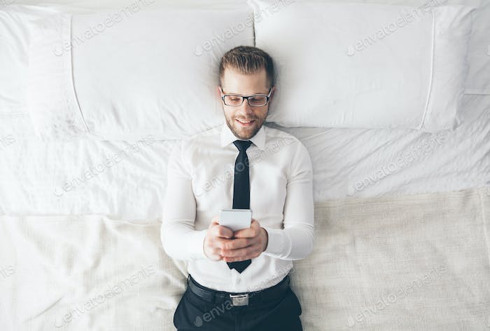 Top view. Handsome businessman with glasses lying on bed texting from his smartphone