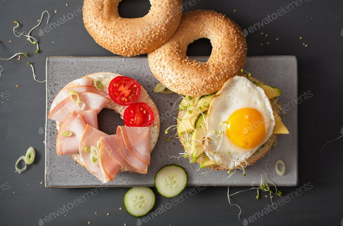 sandwiches on bagels with egg, avocado, soft cheese, alfalfa spr