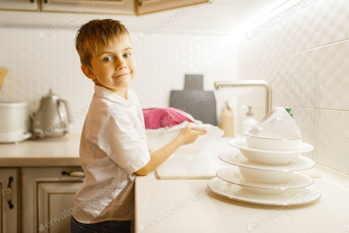 Little boy in gloves washing dishes on the kitchen