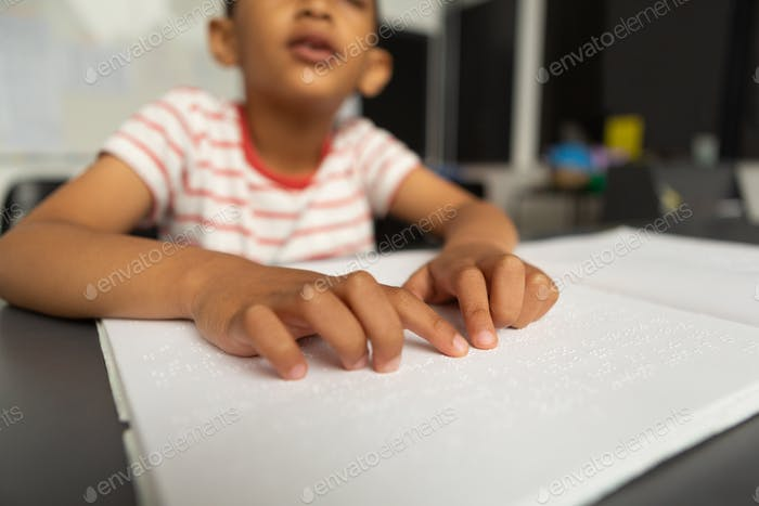 Blind schoolboy hands reading braille book in classroom at elementary school