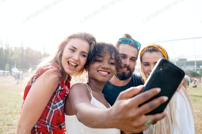 Multiethnische Gruppe junger Menschen, die beim Musikfestival Selfie in die sozialen Medien bringen