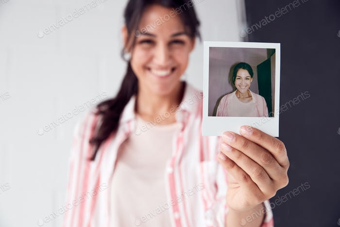 Portrait Of Female Photographer On Photo Shoot Holding Up Instant Polaroid Print In Studio