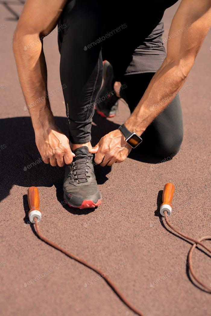 Man tying sneaker shoelace