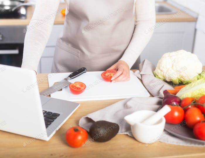 La mujer está cocinando viendo clase culinaria virtual