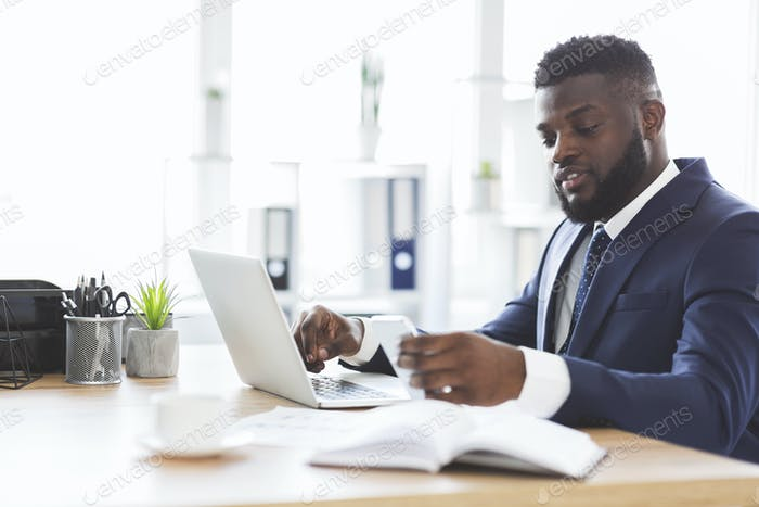 Young businessman checking messages on smartphone at job