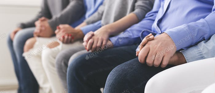Unrecognizable people holding hands at group psychotherapy session