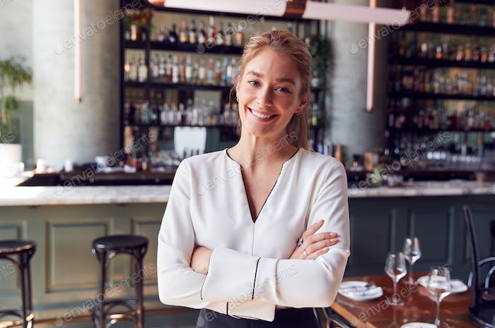 Portrait Of Confident Female Owner Of Restaurant Bar Standing By Counter