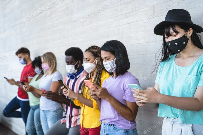 Young people wearing face mask using mobile smartphone outdoor