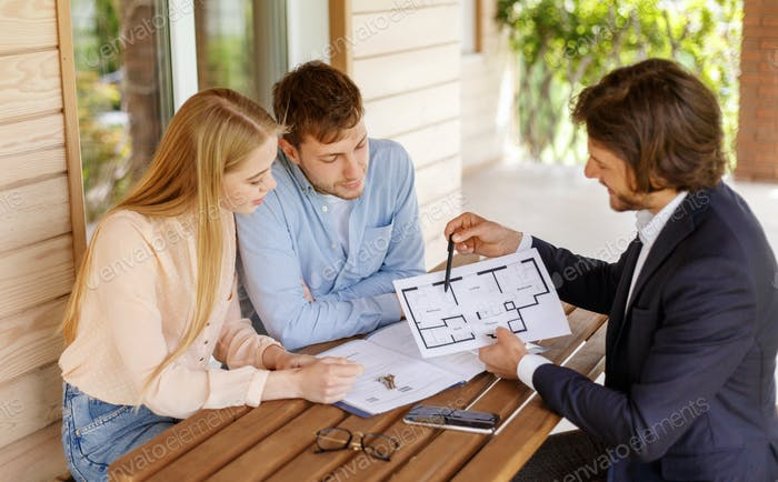 Real estate agent showing house plan to millennial couple at table on porch