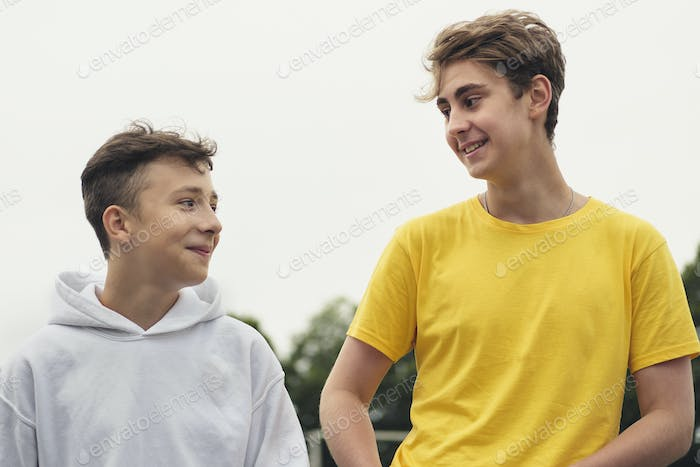 Two happy young teenage boys standing chatting