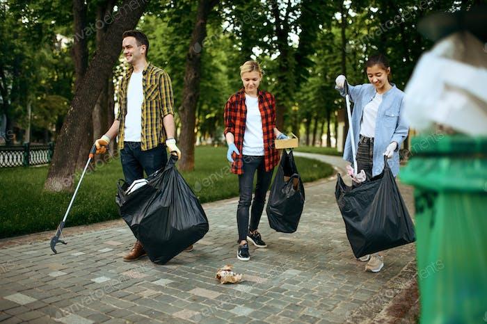 Voluntarios recogiendo basura en bolsas de plástico en el parque