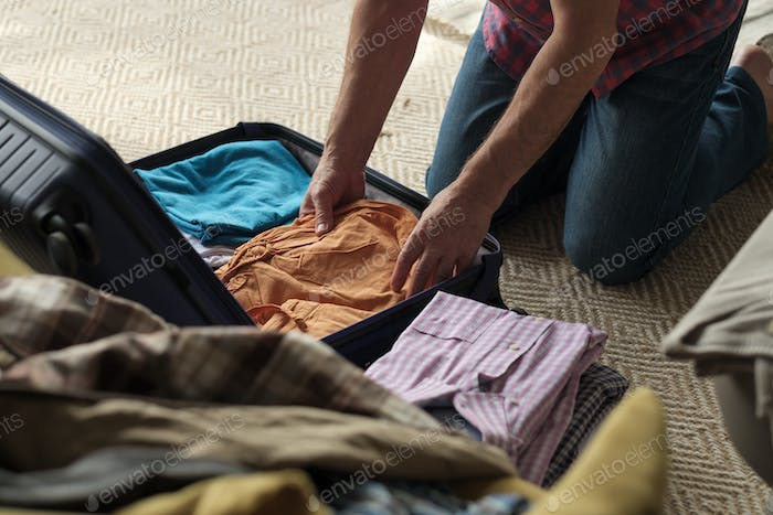 Senior man hands packing clothes in suitcase.