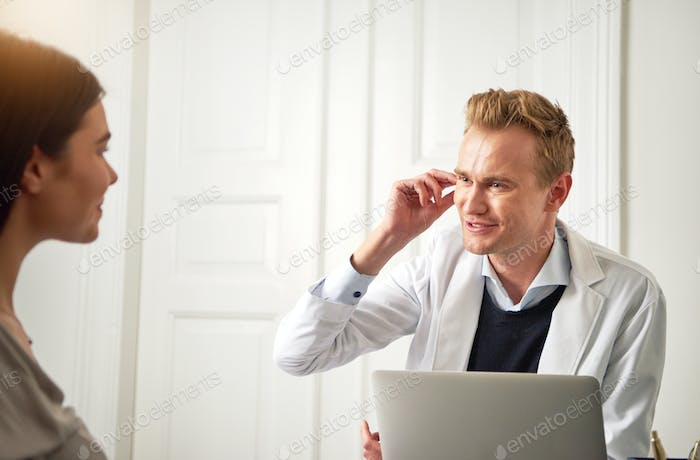 Beautician consulting woman sitting at laptop and touching face