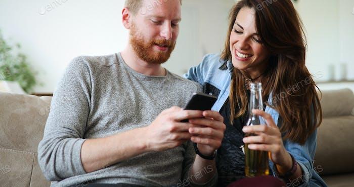 Cheerful couple laughing watching smart phone