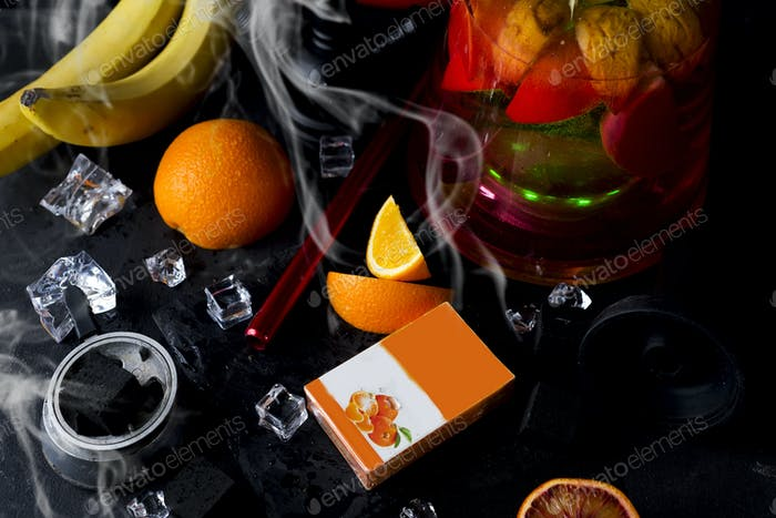 Red hookah with orange and with a box of tobacco and a place for your design on a black background
