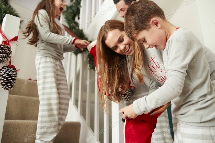 Parents Greeting Excited Children Wearing Pyjamas On Christmas Morning