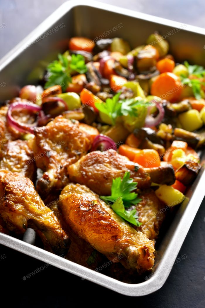 Baked chicken wings with vegetables in baking tray
