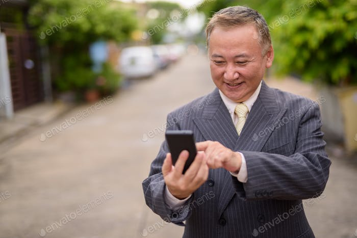 Mature Asian businessman using mobile phone in the streets outdo