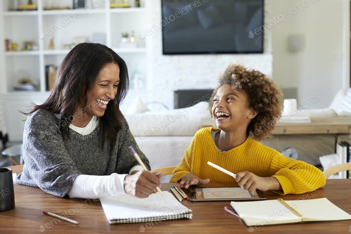 Mixed race woman sitting at a table doing homework with her granddaughter, laughing