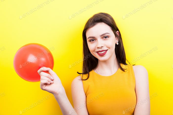 Happy woman playing with a red balloon
