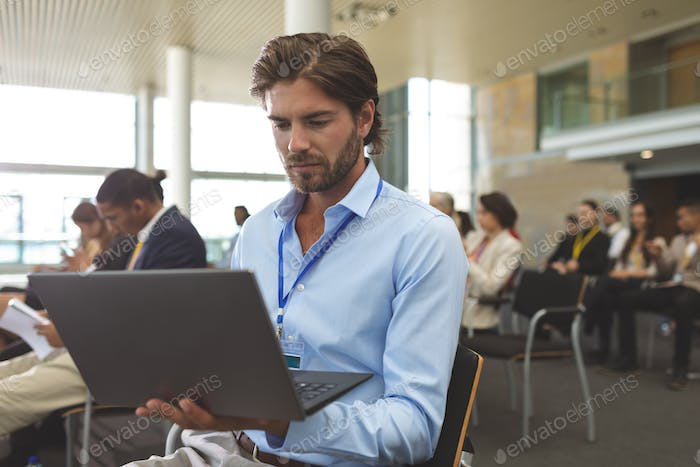 Front view of young Caucasian businessman using laptop during seminar in office building