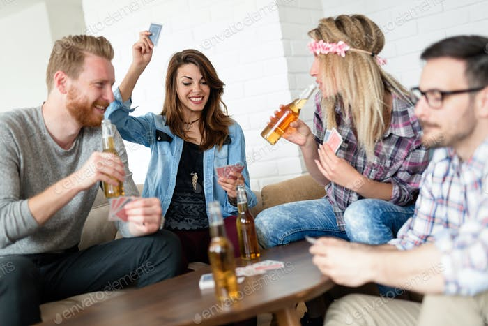 Happy group of friends playing cards and drinking