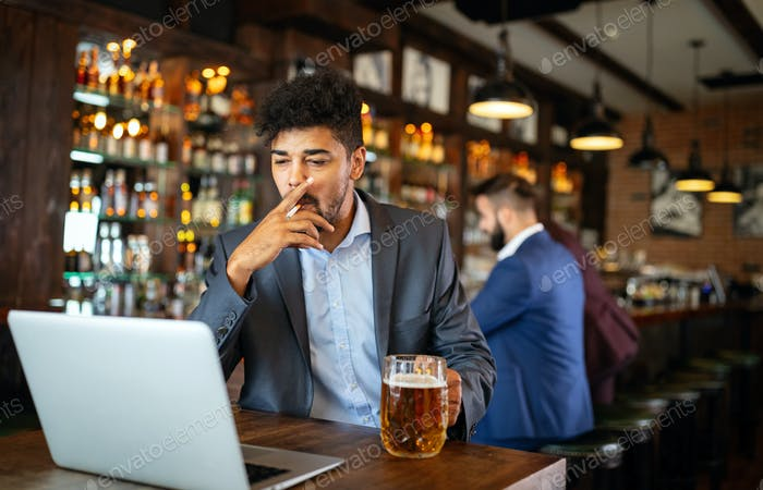 People and bad habits concept. Man drinking beer and smoking cigarette at pub