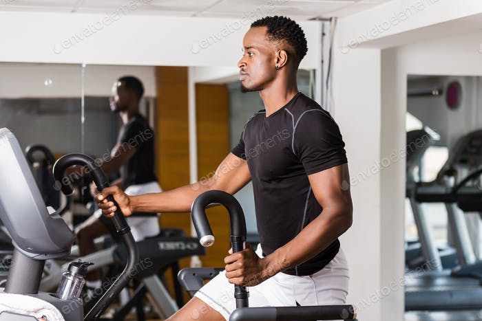 Black African American  young man doing cardio workout at the gy
