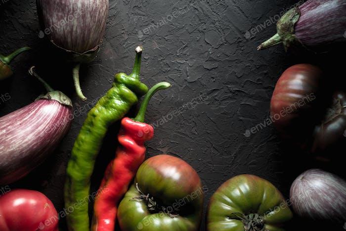 Half-frame of multi-colored eggplant, tomato and chili