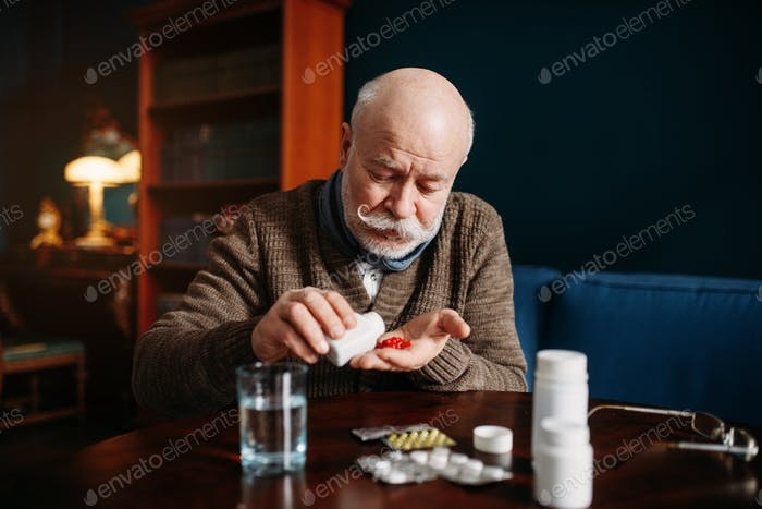 Elderly man hand with pills, age-related diseases
