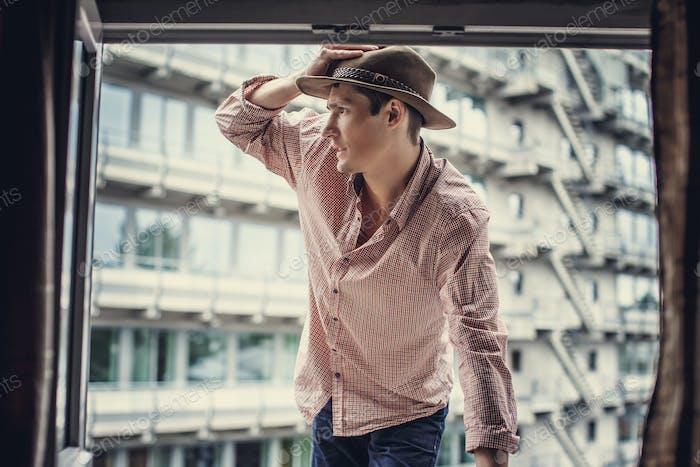 Guy in pink shirt looking through window.