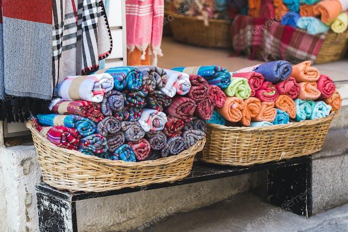 Rolls of multicolor towels in a wicker basket on a shop window