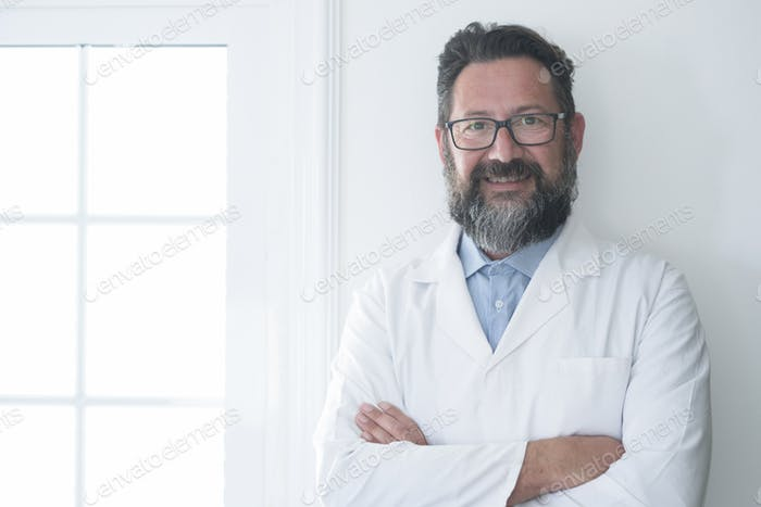Cheerful mature doctor posing and smiling at camera, healthcare and medicine - adult cheerful doc