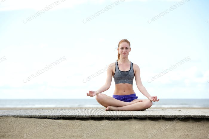 Beautiful young woman sitting outdoors in yoga pose