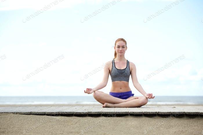 Schöne junge Frau sitzt im Freien in Yoga-Pose