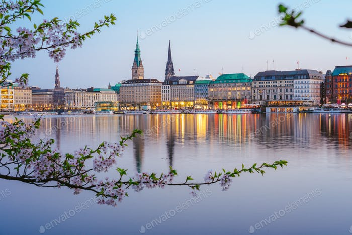 Beautiful panoramic view of calm Alster river with Hamburg town hall - Rathaus behind the buildings