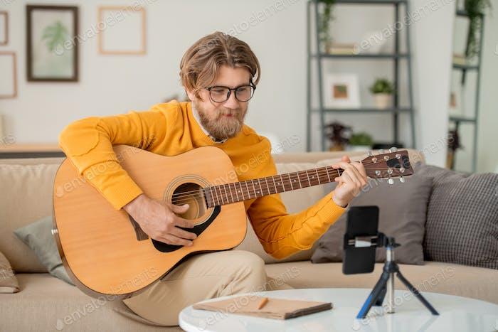 Glücklicher Mann, der in Smartphone-Kamera während der Online-Lektion des Gitarrenspiels sucht