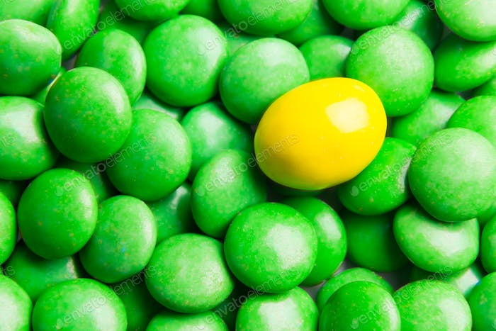 Focus on yellow chocolate candy against heaps of green candies