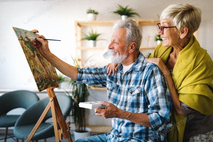 Portrait of smiling beautiful elderly couple painting