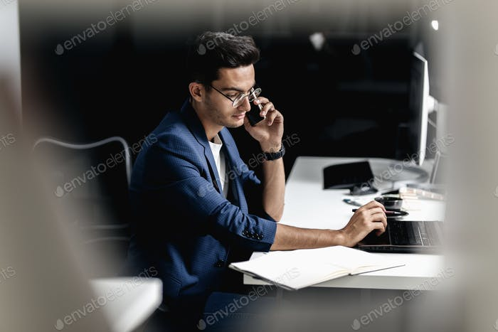 Professional architect dressed in a business suit talking by phone and works on the laptop in the
