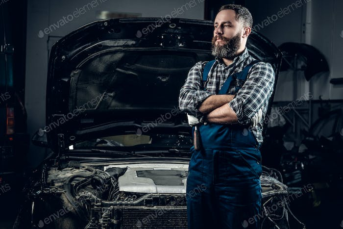 Mechanic in front of a car in a garage.