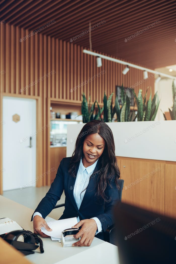 Smiling African American businesswoman sorting documents at a reception desk