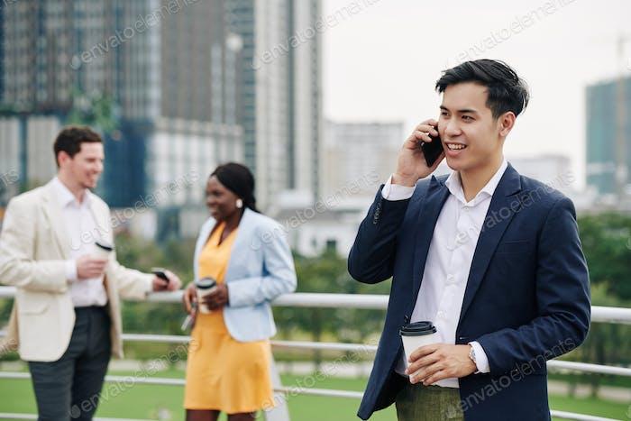 Positive businessman talking on phone