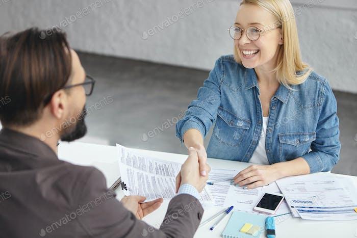 Konzept der Vereinbarung und der Verordnungen von Bussines. Froh, dass blonde erfolgreiche weibliche und männliche Hände schütteln