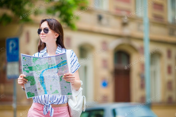 Happy young woman with a city map in Europe. Travel tourist woman with map in Prague outdoors during