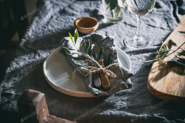 Table setting with white plate, linen napkin, olive brunch Trendy rustic table setting.